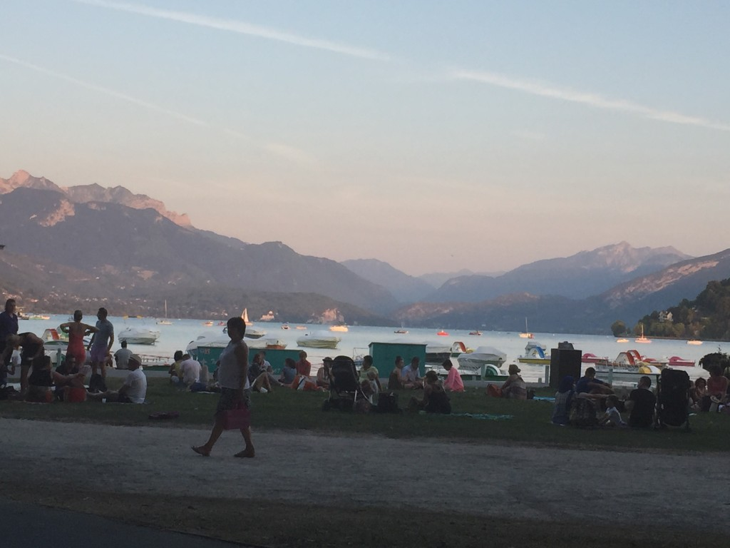 Mountain view in annecy, france. people sitting at the beach